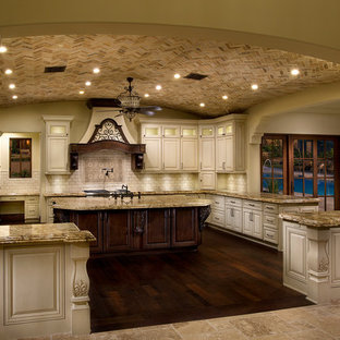Inspiration for an expansive mediterranean u-shaped separate kitchen in Phoenix with a farmhouse sink, louvered cabinets, white cabinets, granite benchtops, beige splashback, mosaic tile splashback, panelled appliances, dark hardwood floors and multiple islands.