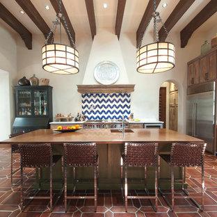 Cette photo montre une cuisine méditerranéenne avec un évier intégré, des portes de placard en bois vieilli, un électroménager en acier inoxydable, un îlot central et un plan de travail en cuivre.
