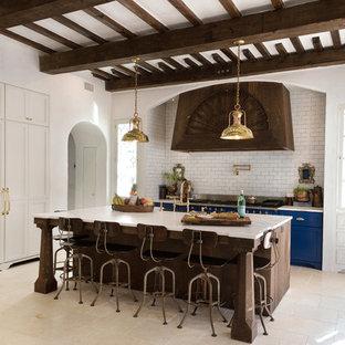 ジャクソンビルの中サイズの地中海スタイルのおしゃれなキッチン (シェーカースタイル扉のキャビネット、白いキャビネット、大理石カウンター、白いキッチンパネル、カラー調理設備、ライムストーンの床、サブウェイタイルのキッチンパネル) の写真