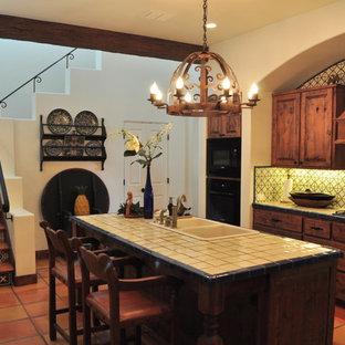 オースティンの中くらいのサンタフェスタイルのおしゃれなキッチン (中間色木目調キャビネット、タイルカウンター、テラコッタタイルの床、ダブルシンク、レイズドパネル扉のキャビネット、マルチカラーのキッチンパネル、セラミックタイルのキッチンパネル、黒い調理設備) の写真