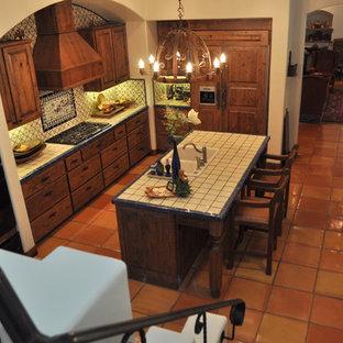 Esempio di una cucina stile americano chiusa e di medie dimensioni con ante in legno scuro, top piastrellato, pavimento in terracotta, lavello a doppia vasca, ante con bugna sagomata, paraspruzzi multicolore, paraspruzzi con piastrelle in ceramica e elettrodomestici neri