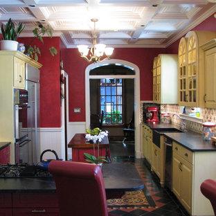 フェニックスの大きいサンタフェスタイルのおしゃれなキッチン (黄色いキャビネット、ソープストーンカウンター、ダブルシンク、レイズドパネル扉のキャビネット、マルチカラーのキッチンパネル、セラミックタイルのキッチンパネル、シルバーの調理設備、テラコッタタイルの床) の写真