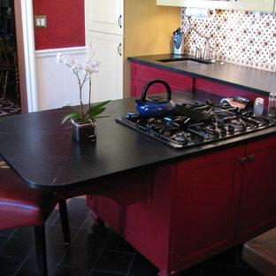 Idéer för ett avskilt, stort amerikanskt parallellkök, med en dubbel diskho, luckor med upphöjd panel, gula skåp, bänkskiva i täljsten, flerfärgad stänkskydd, stänkskydd i keramik, rostfria vitvaror, klinkergolv i terrakotta och en halv köksö