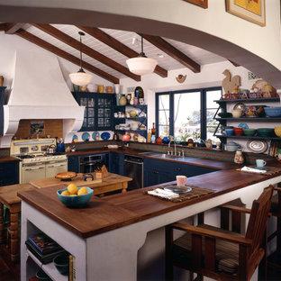 ロサンゼルスの地中海スタイルのおしゃれなキッチン (オープンシェルフ、木材カウンター、ドロップインシンク、青いキャビネット、茶色いキッチンパネル、シルバーの調理設備の) の写真