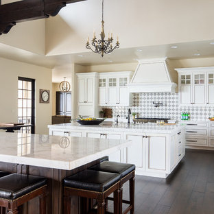 Mediterranean kitchen remodeling - Inspiration for a mediterranean dark wood floor and brown floor kitchen remodel in San Luis Obispo with recessed-panel cabinets, white cabinets, two islands, marble countertops, multicolored backsplash and stainless steel appliances