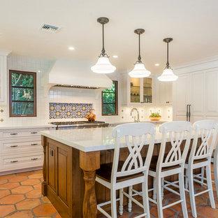 Große Mediterrane Küche mit profilierten Schrankfronten, weißen Schränken, Marmor-Arbeitsplatte, bunter Rückwand, Rückwand aus Zementfliesen, Elektrogeräten mit Frontblende, Terrakottaboden, Kücheninsel und orangem Boden in Los Angeles