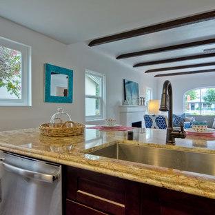 サンディエゴの小さいサンタフェスタイルのおしゃれなキッチン (アンダーカウンターシンク、シェーカースタイル扉のキャビネット、濃色木目調キャビネット、大理石カウンター、ベージュキッチンパネル、石タイルのキッチンパネル、シルバーの調理設備の、無垢フローリング) の写真