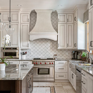 This is an example of a large mediterranean l-shaped kitchen in Tampa with a farmhouse sink, beige cabinets, granite benchtops, white splashback, ceramic splashback, stainless steel appliances, ceramic floors, with island, grey benchtop, raised-panel cabinets and multi-coloured floor.