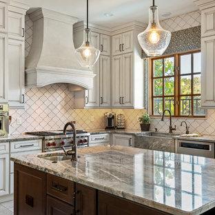 Inspiration för ett stort medelhavsstil grå grått kök, med en rustik diskho, luckor med infälld panel, beige skåp, granitbänkskiva, vitt stänkskydd, stänkskydd i keramik, rostfria vitvaror, klinkergolv i keramik, en köksö och beiget golv