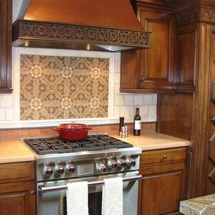 Idéer för mellanstora, avskilda medelhavsstil linjära kök, med luckor med upphöjd panel, skåp i mellenmörkt trä, beige stänkskydd, rostfria vitvaror, en köksö, granitbänkskiva och stänkskydd i mosaik