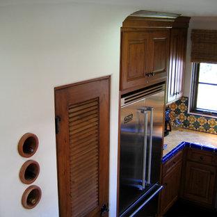 サンタバーバラの小さい地中海スタイルのおしゃれなキッチン (ダブルシンク、レイズドパネル扉のキャビネット、中間色木目調キャビネット、タイルカウンター、セラミックタイルのキッチンパネル、シルバーの調理設備の、濃色無垢フローリング、マルチカラーのキッチンパネル、茶色い床、黄色いキッチンカウンター) の写真