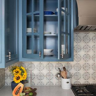 ロサンゼルスの小さい地中海スタイルのおしゃれなキッチン (エプロンフロントシンク、シェーカースタイル扉のキャビネット、青いキャビネット、クオーツストーンカウンター、青いキッチンパネル、セラミックタイルのキッチンパネル、シルバーの調理設備、無垢フローリング、アイランドなし) の写真
