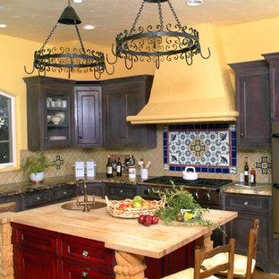 サンフランシスコの地中海スタイルのおしゃれなキッチン (落し込みパネル扉のキャビネット、シルバーの調理設備の、木材カウンター、濃色木目調キャビネット) の写真