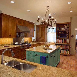 Immagine di una cucina mediterranea di medie dimensioni con lavello a doppia vasca, ante con riquadro incassato, ante in legno bruno, top in onice, paraspruzzi marrone, paraspruzzi con piastrelle in ceramica, elettrodomestici in acciaio inossidabile, pavimento in mattoni e isola