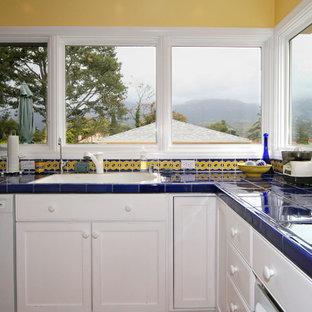 サンタバーバラの中サイズの地中海スタイルのおしゃれなキッチン (白いキャビネット、タイルカウンター、マルチカラーのキッチンパネル、セラミックタイルのキッチンパネル) の写真