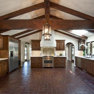 Medelhavsstil inredning av ett stort kök, med en undermonterad diskho, luckor med infälld panel, skåp i slitet trä, marmorbänkskiva, vitt stänkskydd, stänkskydd i tunnelbanekakel, rostfria vitvaror och klinkergolv i terrakotta