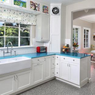 サンフランシスコの中サイズのトランジショナルスタイルのおしゃれなキッチン (エプロンフロントシンク、シェーカースタイル扉のキャビネット、白いキャビネット、白いキッチンパネル、シルバーの調理設備の、リノリウムの床、ターコイズのキッチンカウンター) の写真