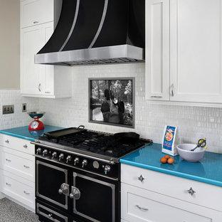 サンフランシスコの中くらいのミッドセンチュリースタイルのおしゃれなキッチン (エプロンフロントシンク、シェーカースタイル扉のキャビネット、白いキャビネット、白いキッチンパネル、セラミックタイルのキッチンパネル、黒い調理設備、リノリウムの床、アイランドなし、ターコイズのキッチンカウンター) の写真