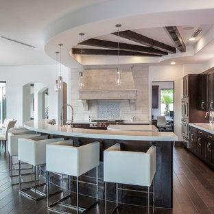 オースティンの広いモダンスタイルのおしゃれなキッチン (ドロップインシンク、フラットパネル扉のキャビネット、茶色いキャビネット、珪岩カウンター、ベージュキッチンパネル、磁器タイルのキッチンパネル、シルバーの調理設備、濃色無垢フローリング、茶色い床、白いキッチンカウンター) の写真