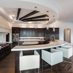 Esempio di una grande cucina moderna con lavello da incasso, ante lisce, ante marroni, top in quarzite, paraspruzzi beige, paraspruzzi in gres porcellanato, elettrodomestici in acciaio inossidabile, parquet scuro, 2 o più isole, pavimento marrone e top bianco