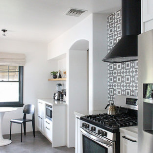 Design ideas for a mid-sized modern galley eat-in kitchen in Los Angeles with a farmhouse sink, shaker cabinets, white cabinets, quartz benchtops, beige splashback, terra-cotta splashback, stainless steel appliances, cement tiles, no island, grey floor and beige benchtop.