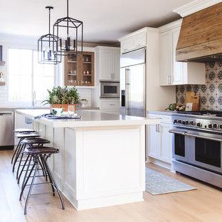 サンディエゴの中サイズのトランジショナルスタイルのおしゃれなキッチン (落し込みパネル扉のキャビネット、白いキャビネット、マルチカラーのキッチンパネル、セメントタイルのキッチンパネル、シルバーの調理設備の、淡色無垢フローリング、ベージュの床、アンダーカウンターシンク、珪岩カウンター) の写真