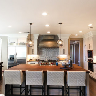 Large modern eat-in kitchen appliance - Eat-in kitchen - large modern l-shaped dark wood floor and brown floor eat-in kitchen idea in San Diego with a farmhouse sink, shaker cabinets, white cabinets, wood countertops, blue backsplash, cement tile backsplash, stainless steel appliances, an island and brown countertops