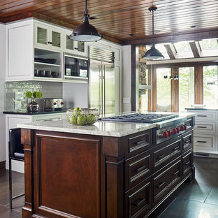 Mid-sized modern eat-in kitchen ideas - Inspiration for a mid-sized modern galley porcelain floor eat-in kitchen remodel in Richmond with a farmhouse sink, raised-panel cabinets, dark wood cabinets, quartzite countertops, gray backsplash, subway tile backsplash, stainless steel appliances and an island