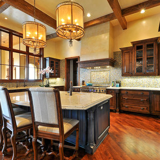 Example of a huge mountain style u-shaped medium tone wood floor eat-in kitchen design in Austin with an undermount sink, raised-panel cabinets, medium tone wood cabinets, granite countertops, multicolored backsplash, glass tile backsplash, paneled appliances and an island
