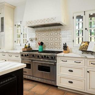 Inspiration för stora medelhavsstil vitt kök, med luckor med infälld panel, beige skåp, bänkskiva i kvartsit, vitt stänkskydd, stänkskydd i tunnelbanekakel, rostfria vitvaror, en köksö, en rustik diskho, klinkergolv i terrakotta och brunt golv