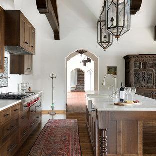Zweizeilige, Große Mediterrane Küche mit Landhausspüle, Schrankfronten mit vertiefter Füllung, dunklen Holzschränken, Küchengeräten aus Edelstahl, dunklem Holzboden, Kücheninsel, braunem Boden, weißer Arbeitsplatte, Marmor-Arbeitsplatte und Küchenrückwand in Weiß in Minneapolis