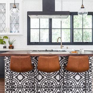 サクラメントの地中海スタイルのおしゃれなキッチン (エプロンフロントシンク、ガラス扉のキャビネット、白いキャビネット、大理石カウンター、白いキッチンパネル、大理石の床、無垢フローリング、茶色い床、白いキッチンカウンター、シルバーの調理設備の) の写真