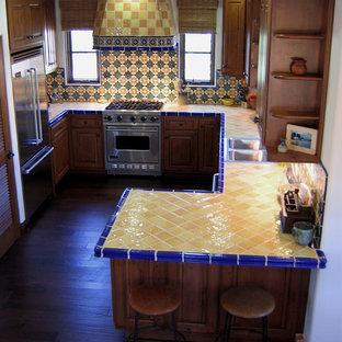 Inredning av ett medelhavsstil litet gul gult kök, med en dubbel diskho, luckor med upphöjd panel, skåp i mellenmörkt trä, kaklad bänkskiva, stänkskydd i keramik, rostfria vitvaror, mörkt trägolv, en halv köksö, flerfärgad stänkskydd och brunt golv