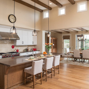 Mediterranean eat-in kitchen remodeling - Inspiration for a mediterranean medium tone wood floor eat-in kitchen remodel in San Diego with an undermount sink, shaker cabinets, white cabinets, beige backsplash, stainless steel appliances, an island and brown countertops