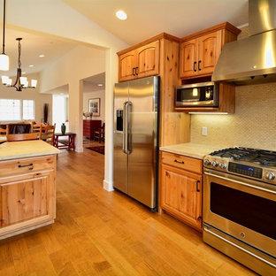ロサンゼルスのサンタフェスタイルのおしゃれなキッチン (シェーカースタイル扉のキャビネット、淡色木目調キャビネット、ベージュキッチンパネル、セラミックタイルのキッチンパネル、シルバーの調理設備の、淡色無垢フローリング) の写真