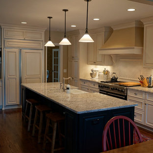 Mid-sized traditional eat-in kitchen photos - Mid-sized elegant l-shaped medium tone wood floor eat-in kitchen photo in Chicago with a farmhouse sink, raised-panel cabinets, white cabinets, granite countertops, white backsplash, subway tile backsplash, stainless steel appliances and an island