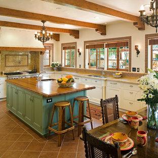Große Landhausstil Wohnküche in U-Form mit Unterbauwaschbecken, profilierten Schrankfronten, grünen Schränken, Arbeitsplatte aus Holz, Rückwand aus Terrakottafliesen, Küchengeräten aus Edelstahl, Porzellan-Bodenfliesen und Kücheninsel in San Diego