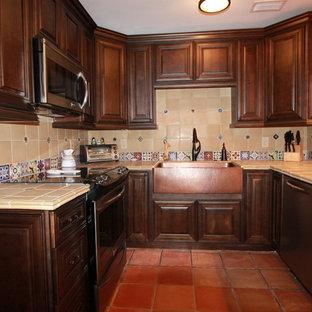 Esempio di una cucina rustica di medie dimensioni con lavello stile country, ante con bugna sagomata, ante in legno scuro, top piastrellato, paraspruzzi beige, paraspruzzi con piastrelle in ceramica, elettrodomestici in acciaio inossidabile e pavimento in terracotta
