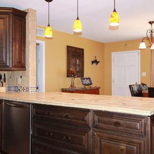 タンパの中サイズのラスティックスタイルのおしゃれなキッチン (エプロンフロントシンク、レイズドパネル扉のキャビネット、中間色木目調キャビネット、タイルカウンター、ベージュキッチンパネル、セラミックタイルのキッチンパネル、シルバーの調理設備の、テラコッタタイルの床) の写真