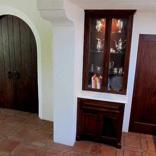 サンタバーバラの小さい地中海スタイルのおしゃれなキッチン (アンダーカウンターシンク、レイズドパネル扉のキャビネット、大理石カウンター、白いキッチンパネル、黒い調理設備、テラコッタタイルの床、アイランドなし、濃色木目調キャビネット、サブウェイタイルのキッチンパネル、赤い床、白いキッチンカウンター) の写真