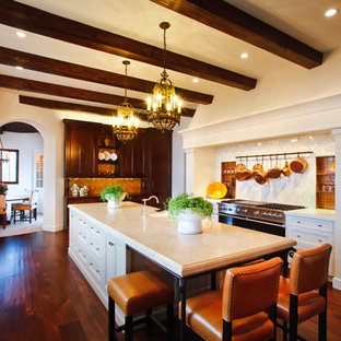 This is an example of a large mediterranean kitchen in Los Angeles with a farmhouse sink, recessed-panel cabinets, beige cabinets, limestone benchtops, orange splashback, ceramic splashback, panelled appliances, medium hardwood floors, with island, brown floor and beige benchtop.