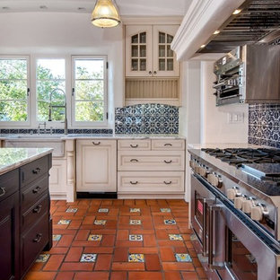 Mediterranean kitchen remodeling - Tuscan terra-cotta tile kitchen photo in San Francisco with a farmhouse sink, white cabinets, blue backsplash and stainless steel appliances