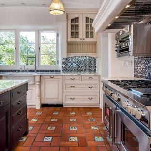 Inspiration för ett medelhavsstil kök, med en rustik diskho, vita skåp, blått stänkskydd, rostfria vitvaror och klinkergolv i terrakotta