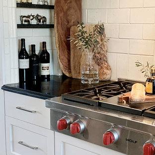 フェニックスの広いトランジショナルスタイルのおしゃれなキッチン (一体型シンク、落し込みパネル扉のキャビネット、白いキャビネット、御影石カウンター、白いキッチンパネル、セラミックタイルのキッチンパネル、シルバーの調理設備、ライムストーンの床、ベージュの床、黒いキッチンカウンター、格子天井) の写真