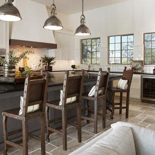 Klassisk inredning av ett stort svart svart kök, med vita skåp, vitt stänkskydd, rostfria vitvaror, en köksö, en integrerad diskho, luckor med infälld panel, granitbänkskiva, stänkskydd i keramik, kalkstensgolv och beiget golv