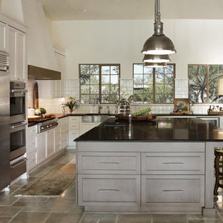 This is an example of a large transitional l-shaped eat-in kitchen in Phoenix with an integrated sink, recessed-panel cabinets, white cabinets, granite benchtops, white splashback, ceramic splashback, stainless steel appliances, limestone floors, with island, beige floor, black benchtop and coffered.