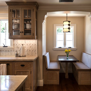 This is an example of a mid-sized mediterranean u-shaped eat-in kitchen in Santa Barbara with an integrated sink, beige cabinets, quartzite benchtops, white splashback, mosaic tile splashback, stainless steel appliances, medium hardwood floors, with island and glass-front cabinets.