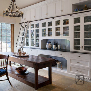 Inspiration for a large classic u-shaped kitchen pantry in Santa Barbara with glass-front cabinets, white cabinets, soapstone worktops, slate flooring, an island, green floors and black worktops.