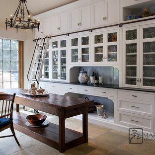 Große Klassische Küche in U-Form mit Vorratsschrank, Glasfronten, weißen Schränken, Speckstein-Arbeitsplatte, Schieferboden, Kücheninsel, grünem Boden und schwarzer Arbeitsplatte in Santa Barbara