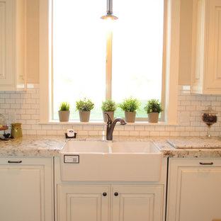 Idéer för mellanstora vintage kök, med en integrerad diskho, luckor med upphöjd panel, gula skåp, granitbänkskiva, vitt stänkskydd, stänkskydd i terrakottakakel, integrerade vitvaror, laminatgolv och en köksö